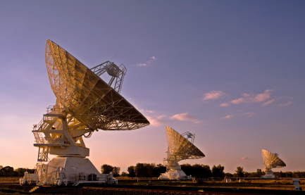 three radio telescopes photographed at sunset